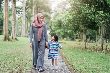 quality time veiled mother with little daughter go to park