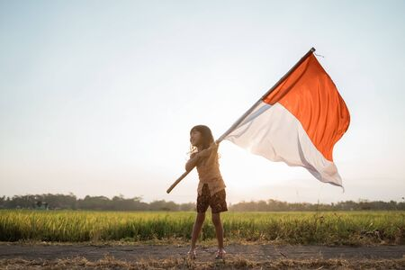 asian little girl flapping Indonesian flag Banco de Imagens