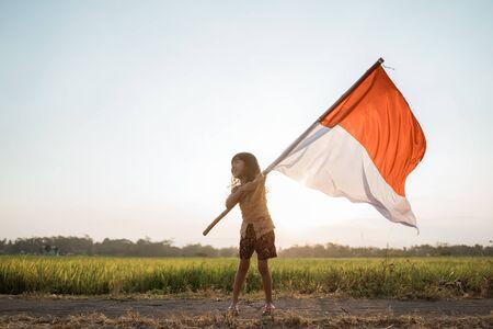 asiatisches kleines Mädchen, das indonesische Flagge flattert