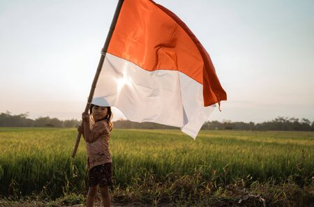 asian little girl flapping Indonesian flag 写真素材