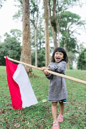 Little girl pride flapping Indonesian flag with happiness