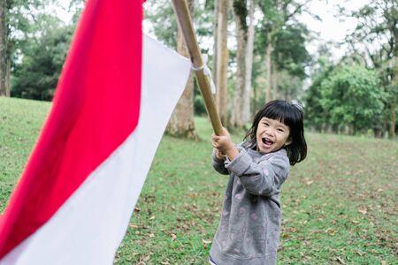 asian little girl flapping Indonesian flag Zdjęcie Seryjne