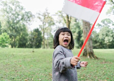 asian little girl holding a stick of Indonesian flag with toothy Zdjęcie Seryjne
