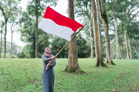 asian veiled woman flapping Indonesian flag