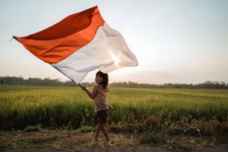 asian little girl flapping Indonesian flag Stock fotó