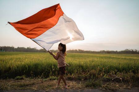 Niña asiática ondeando la bandera de Indonesia