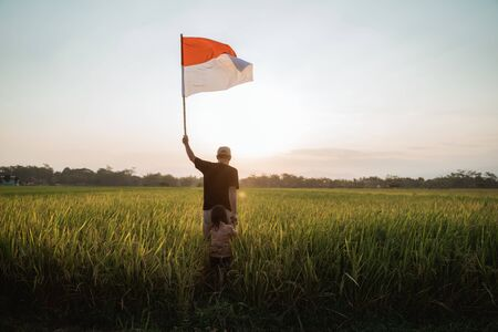 father carrying little girl pride flapping Indonesian flag with happiness Stockfoto