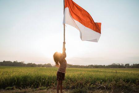 Orgullo de niña agitando la bandera de Indonesia con felicidad Foto de archivo