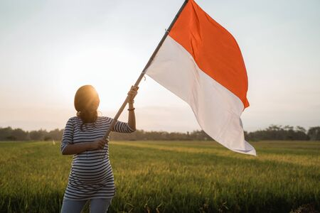 asian young woman flapping Indonesian flag