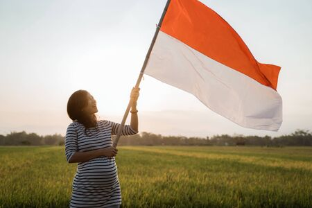 Indonesian pregnant woman holding bamboo stick with big flag