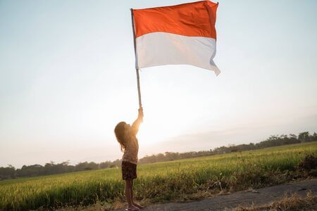 asian little girl flapping Indonesian flag 版權商用圖片