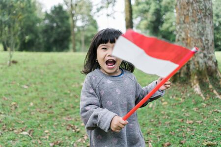 asian little girl holding a stick of Indonesian flag with toothy 스톡 콘텐츠