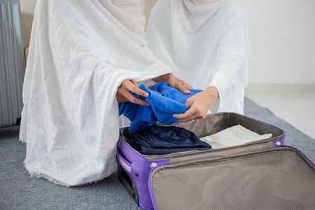 muslim family in white traditional clothes preparing luggage before hajj in Mecca Zdjęcie Seryjne