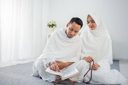 asian wife and husband praying with Al-Quran and tasbih