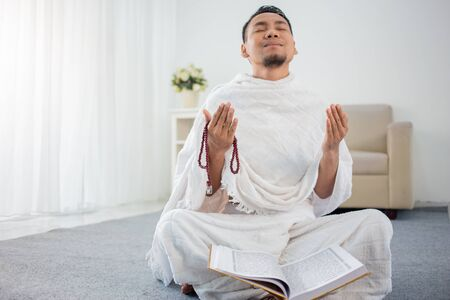 asian young man praying with Al-Quran and prayer beads