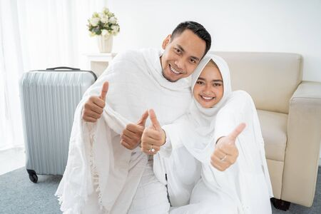 muslim couple sit wearing white traditional with hands thumb up