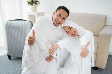 muslim pilgrims wife and husband with thumb up