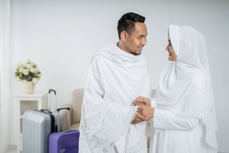 muslim pilgrims wife and husband in white traditional clothes Stock Photo