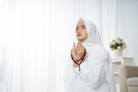 Mujer joven musulmana rezando con ropas tradicionales blancas
