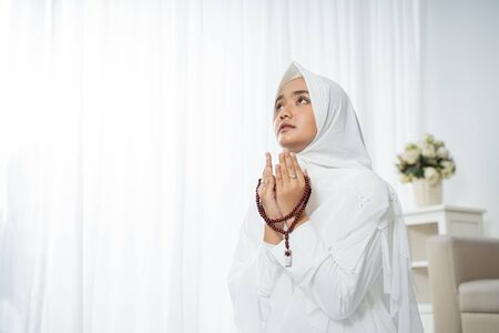 Muslim young woman praying in white traditional clothes Imagens