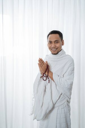 pose muslim asian man standing with tasbih