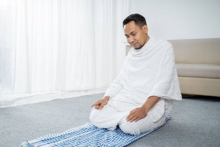 muslim man pray wearing white traditional clothes Ihram