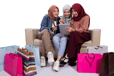 Asian veiled women buying at an online shop