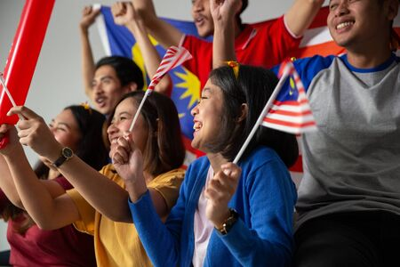 excited asian young supporter holding malaysia flag