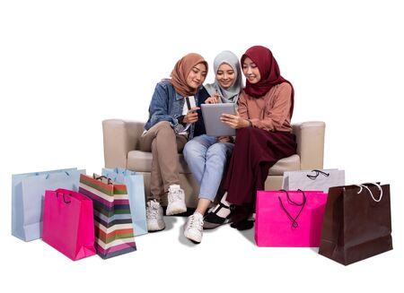 Trois femmes voilées assises près de sacs en papier et tenant une carte de crédit pour acheter dans une boutique en ligne