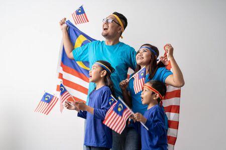 familia de malasia con atributos y bandera celebrando Foto de archivo