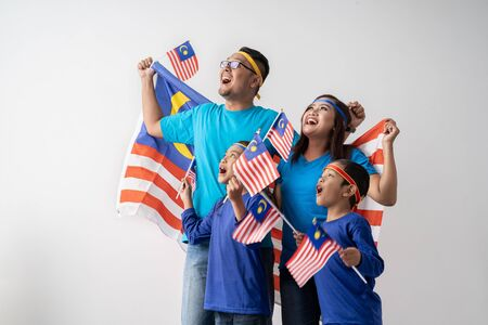 malaysian family holding malaysia flag over white background