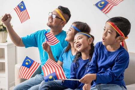 family with malaysia flag sitting on a couch watching soccer