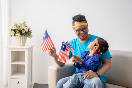 father and son holding malaysian flag together while watching soccer match Banco de Imagens