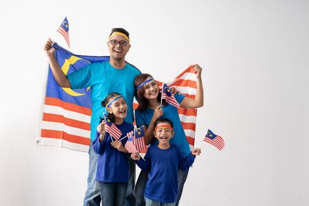 Familia de Malasia sosteniendo la bandera de Malasia sobre fondo blanco.