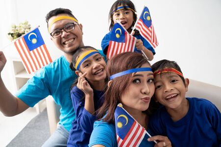 family with malaysian flag take selfie together