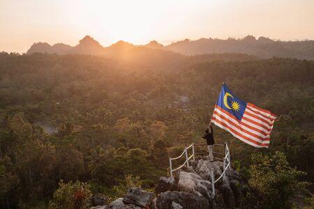 산 꼭대기에 말레이시아의 말레이시아 국기를 가진 남자