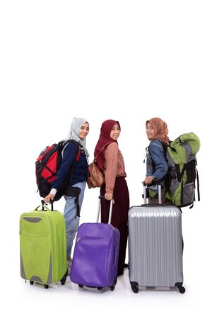 Vista posterior, tres mujer hijab de pie sosteniendo la maleta y la bolsa de transporte