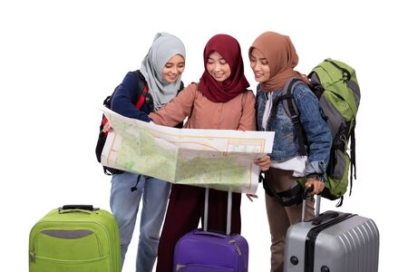 Three hijab traveller holding a map find a holiday destination