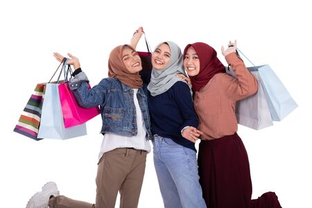 Three veiled women excited when carrying paper bag 写真素材