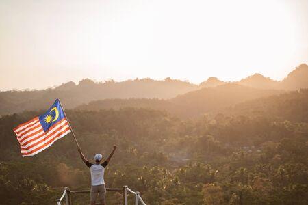 독립 기념일을 축하하는 말레이시아 국기를 가진 아시아 남성