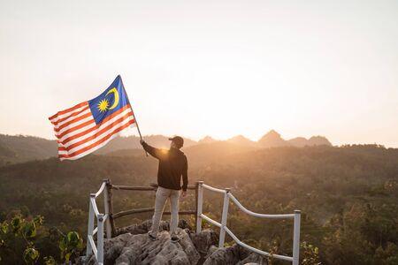 Hombre con bandera de Malasia de Malasia en la cima de la montaña Foto de archivo