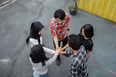 young people putting their hands together