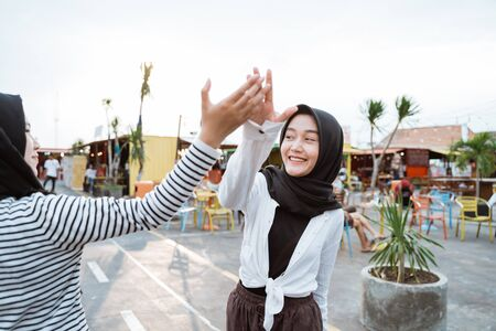 young hijab woman high five with friends