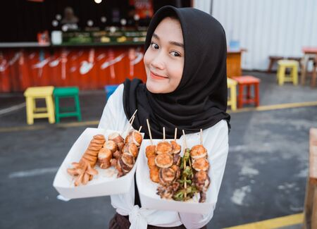 Young woman served Korean street food dish