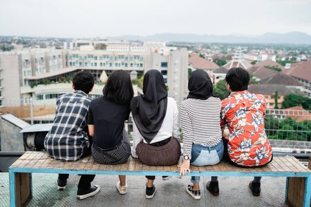 Rear view of young friends sitting together on rooftop