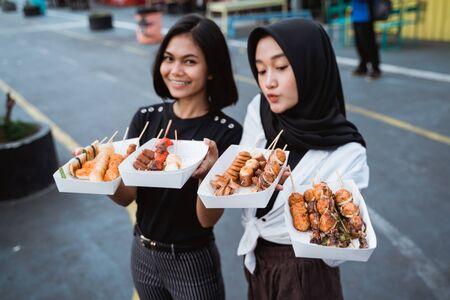two woman served Korean street food dish