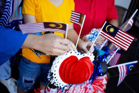 close up of hand decorating some malaysia flag on bicycle