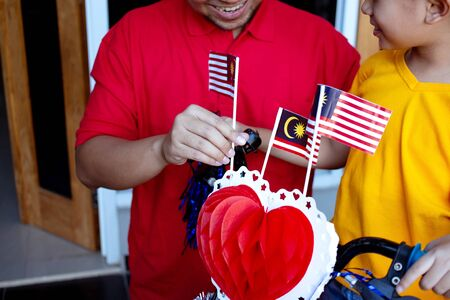 fahter and son decorating bicycle with malaysia flag for independence day party Reklamní fotografie