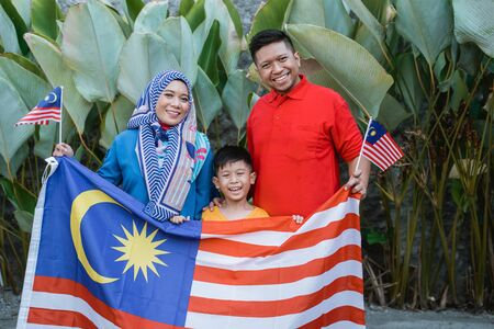 Malaysian family holding malaysia flag in front of their house