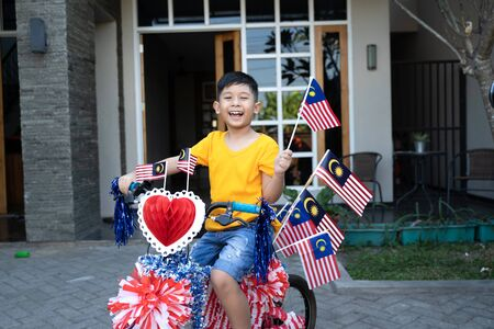 Boy riding his bicycle full with malaysia flag